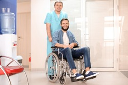 Male doctor taking care of man in wheelchair indoors