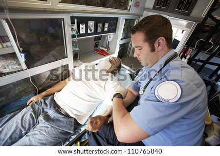 Male doctor taking pulse of a man inside ambulance - stock photo