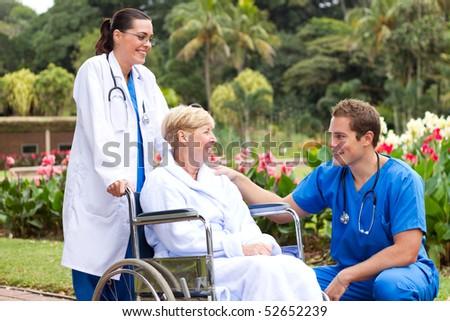 male doctor talking to senior patient in hospital garden