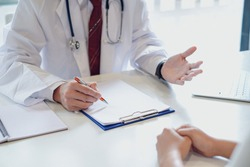 Male doctor was inquiring about the symptom of the patient and notes in the document.