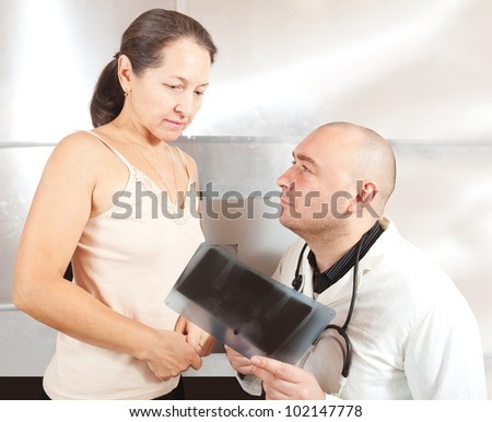 Male doctor with patient looking x-ray scan