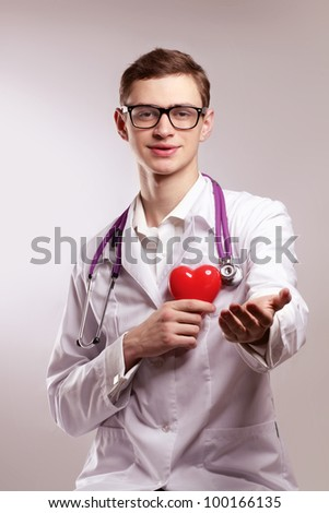 Male doctor with stethoscope holding heart on white background.