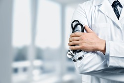 Male doctor with stethoscope on blurred hospital