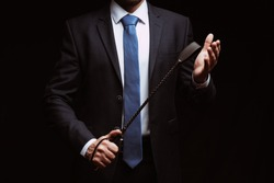 male dominant holds a leather whip Flogger