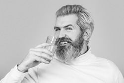 Male drinking from a glass of water. Health care concept photo, lifestyle, close up. Happy beard man drinking water. Smiling male holding transparent glass in her hand. Black and white.