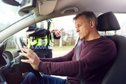 Male Driver Being Stopped By Female Traffic Police Officer With Digital Tablet For Driving Offence
