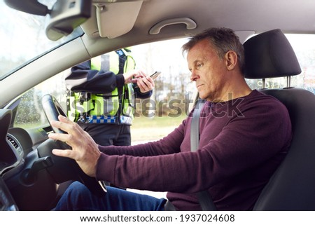 Male Driver Being Stopped By Female Traffic Police Officer With Digital Tablet For Driving Offence Foto d'archivio ©