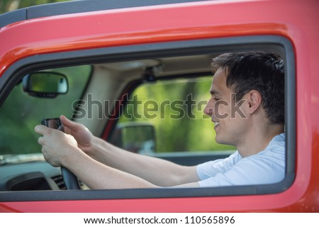 Male Driver Holding Cellphone Texting by Wheel Driving