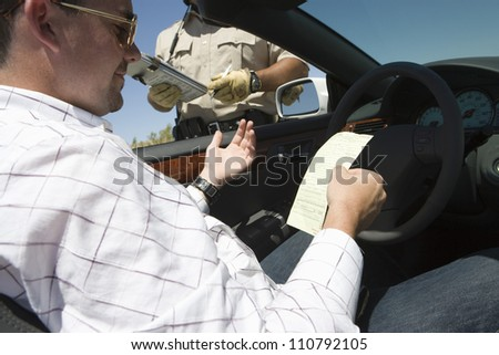 Male driver reading ticket with policeman standing by his car
