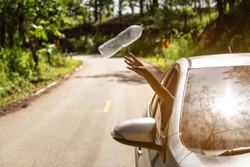 Male driver throwing away plastic bottle from car window on the road,man's hand or arm throwing garbage while driving on valley road in green nature,environmental protection,global warming concept