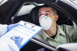 Male driver wearing protective N95 face mask sitting by left drive wheel in UK drive-thru COVID-19 test centre,answering health check up questions,medical worker ticking off symptoms on clipboard form