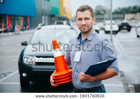 Male driving instructor standing with orange traffic cones and clipboard in his hands. Caucasian man working in driving school. Blurred gray car in background.