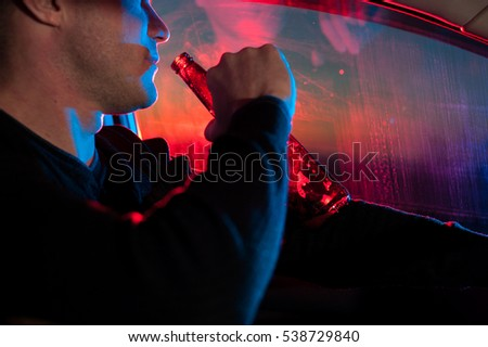 Male drunk driver with beer bottle in car on the background of police car lighting. #538729840