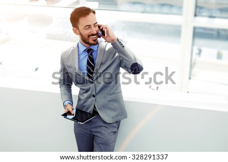 Male economist talking on cell telephone while standing with touch pad in modern interior with copy space area, young successful men entrepreneur speaking on mobile phone during work on digital tablet
