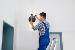 Male Electrician Standing On Stepladder Repairing Light