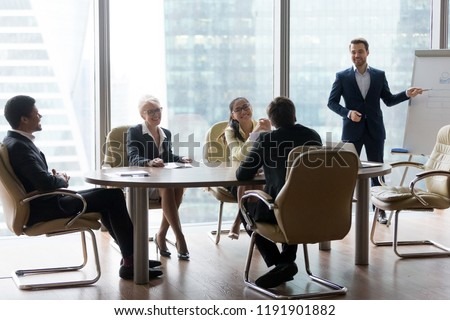 Male employee give flipchart presentation to smiling colleagues at negotiations, man present project or idea to happy coworkers at briefing, workers laugh at office meeting, having casual talk