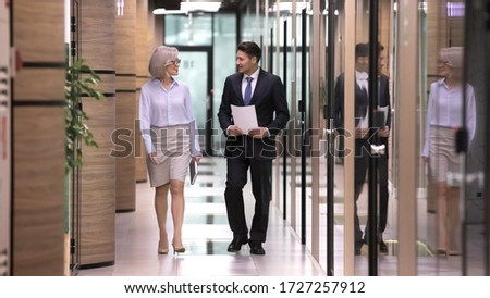 Male employee subordinate and businesslady boss chatting walk in office hallway. Full length mature millennial workers going in workspace hall having business conversation enjoy informal friendly talk