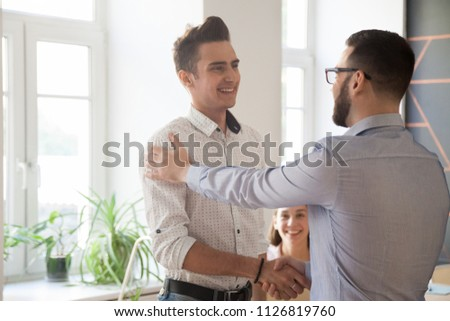Male employer shaking hand of proud worker, congratulating with high work results or achievements, boss handshaking happy satisfied intern greeting with job promotion. Concept of rewarding