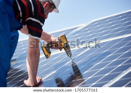 Male engineer in protective helmet installing solar photovoltaic panel system using screwdriver. Electrician mounting blue solar module on roof of modern house. Alternative energy ecological concept. Photo stock ©