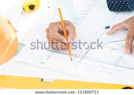Male engineer taking measurements and drawing precise lines