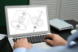 Male engineer working with 3d model of modern equipment on laptop in office, closeup