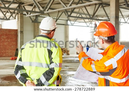 male engineers construction foreman managers outdoors at building site with blueprints