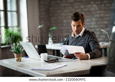 Male entrepreneur analyzing business reports while doing paperwork at his desk in the office.