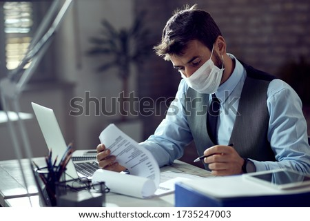Male entrepreneur analyzing business reports while wearing face mask and working in the office during virus epidemic.