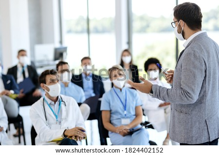 Male entrepreneur holding a training class to large group of healthcare workers and business people in conference hall. They are all wearing protective face mask due to COVID-19 pandemic.