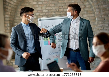 Male entrepreneurs with protective face masks elbow bumping while greeting on a business meeting in the office.,