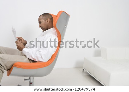 Male executive on modern chair reading document