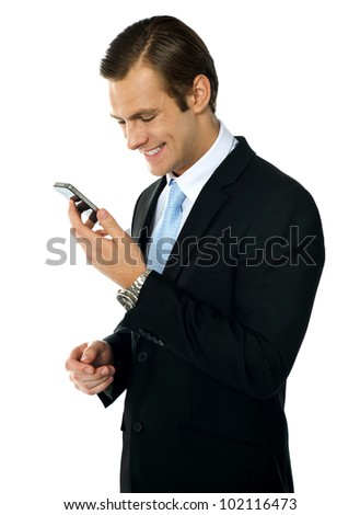 Male executive smiling as he reads message on his mobile. Isolated over white