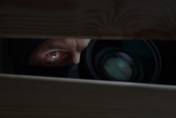 Male eye and camera close-up. Recording to a hidden camera. Private detective with camera looks at a cleft. Espionage background. The concept of eavesdropping, espionage, gossip and the yellow press