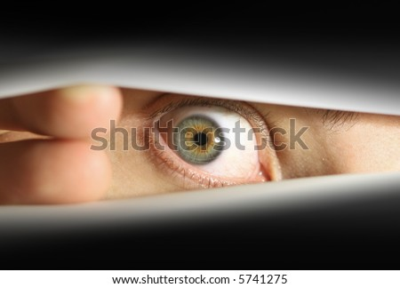 Male eye peering into envelope/package or peering through blinds
