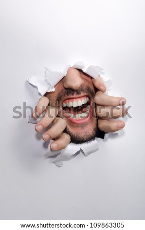 Male face through the hole in paper - stock photo