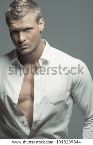 Male fashion, beauty concept. Portrait of brutal young man with short wet blond hair wearing white shirt, posing over gray background. Classic style. Studio shot