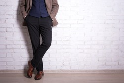 male fashion concept - close up of male legs in business suit and shoes over brick wall
