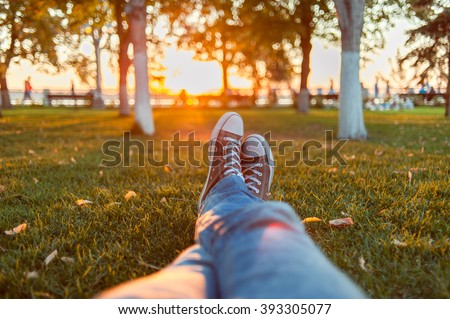 Male feet in gumshoes on green grass in the park at sunset #393305077