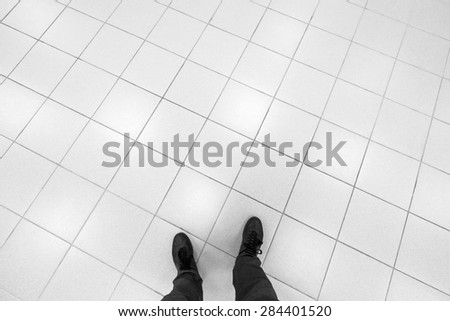 Male feet stand on office floor with white shining square tiling