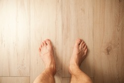 Male feet stand on wooden floor, top view