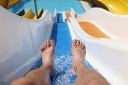 Male feet with splashing water on slide in water park. Entertainment in hotel pools and aquapark concept