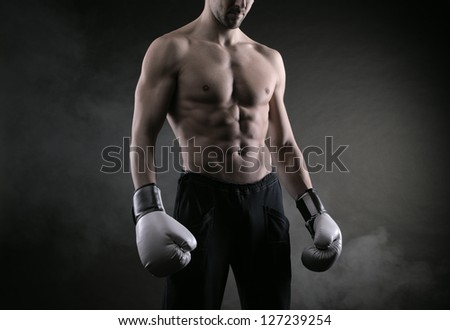 Male fighter posing in front of a dark background