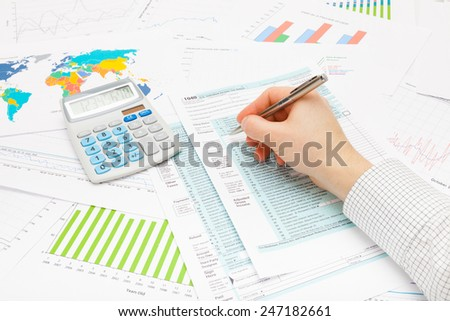Male filling out 1040 US Tax Form with silver ball pen