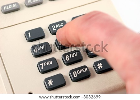 Male finger dialing a 5 on a touch tone phone