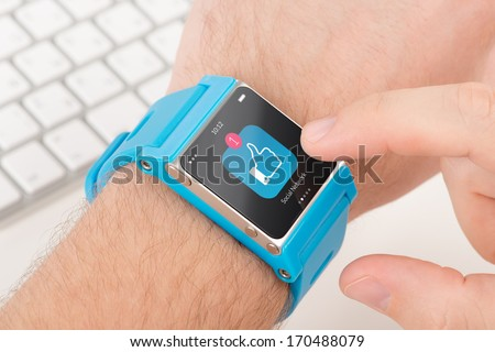 Male finger taps like icon on blue smart watch