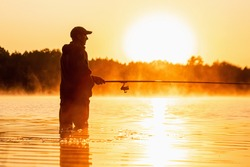 Male fisherman at dawn on the lake catches a fishing rod. Fishing hobby vacation concept. Copy space