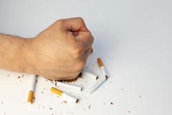 male fist breaks cigarettes on white background