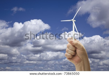 Male Fist Holding Wind Turbine Outside with Clouds and Sky.