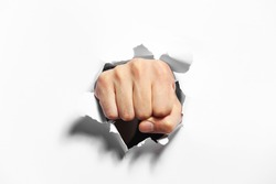Male fist punching through paper, isolated on white