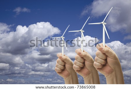 Male Fists Holding Three Wind Turbines Outside with Clouds and Sky.